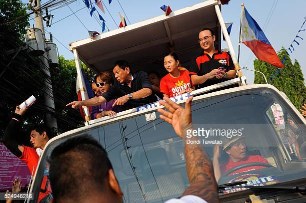 Philippine presidential candidate Rodrigo Duterte gestures to the crowd during a campaign motorcade near a port area on April 27 2016 in Manila...
