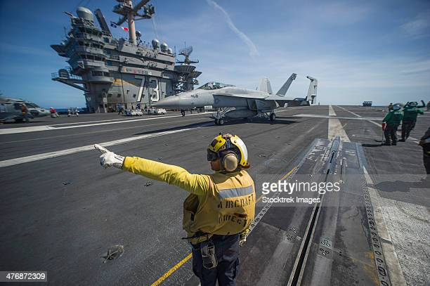 Philippine Sea, August 22, 2013 - Aviation Boatswain's Mate directs an F/A-18E Super Hornet on the flight deck of the aircraft carrier USS George Washington.