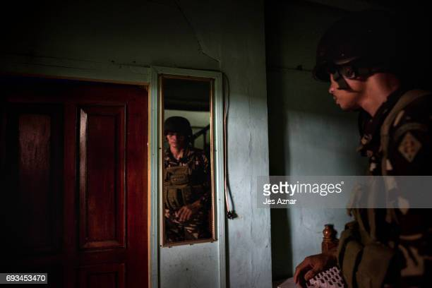 Philippine security forces inspect inside empty houses within the vicinity of a military camp and a hospital for guns and ammunition which the enemy...