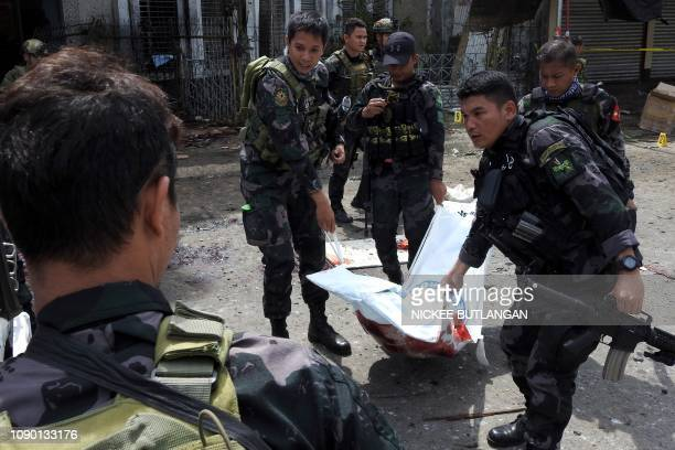 Philippine security personnel carry a body bag containing the remains of a blast victim after two bombs exploded at a church in Jolo Sulu province on...