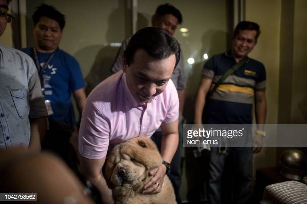 Philippine senator Antonio Trillanes cuddles his dog named Bruno after arriving at his house in Antipolo east of Manila on September 29 2018 Lawmaker...