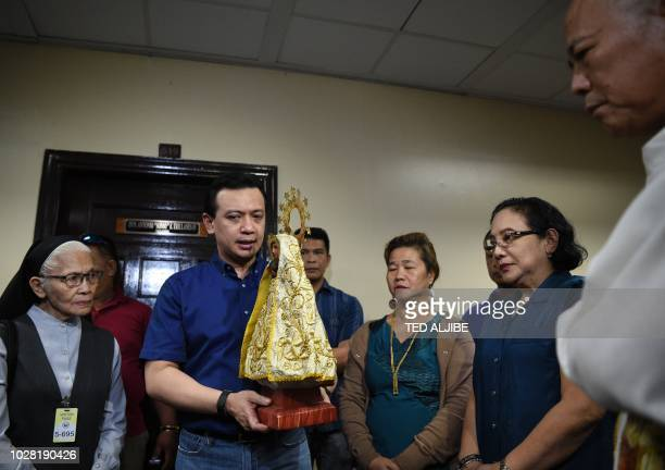 Philippine Senator Antonio Trillanes speaks as he holds the statue of the Virgin Mary of Penafrancia during a meeting with supporters at the senate...