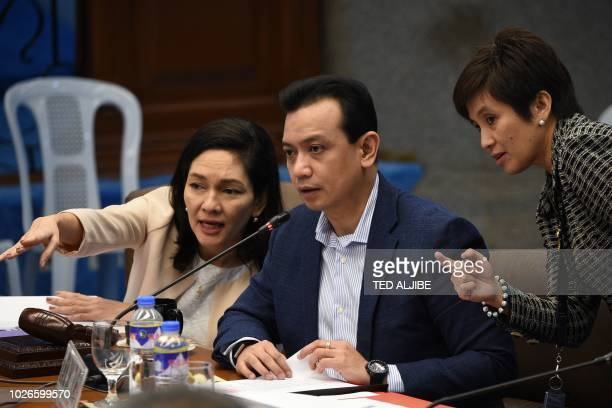 Philippine Senator Antonio Trillanes speaks with Senator Risa Hontiveros during a hearing at the Senate in Manila on September 4 2018 Philippine...