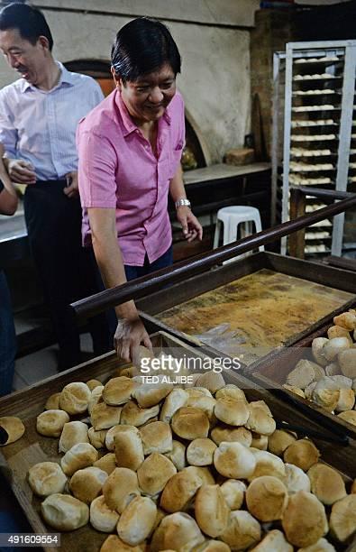 Philippine Senator Ferdinand 'Bongbong' Marcos Jnr the son of late Philippine dictator Ferdinand Marcos tries a 'pandesal' inside a bakery after...