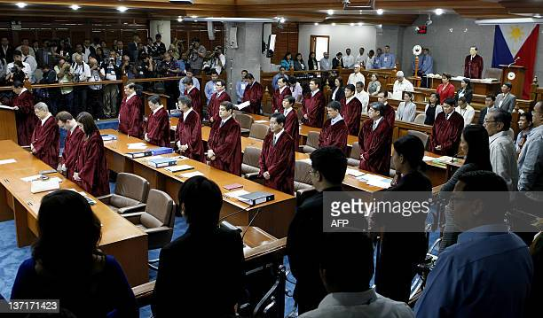 Philippine senators led by Senate President Juan Ponce Enrile stand for an invocation at the start of the impeachment trial for Philippine Supreme...