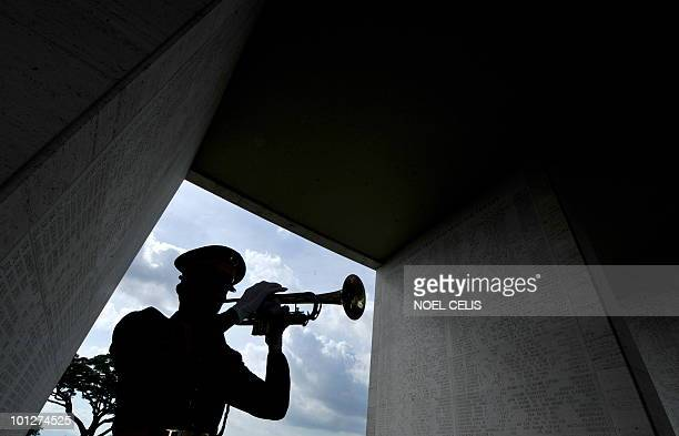 A Philippine soldier blows his bugle along the halls displaying engraved names of soldiers fallen during the World War II at the commemoration of US...