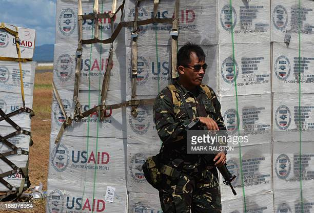 Philippine soldier guards US Aid in the aftermath of Typhoon Haiyan at Tacloban airport on November 15, 2013. The Philippines raised its official...