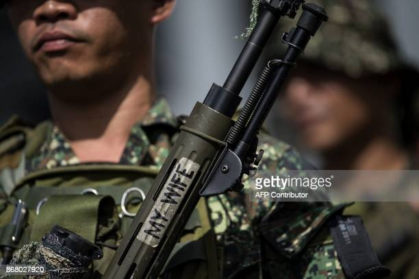 A Philippine soldier holds his sniper rifle with a sticker with words written that reads 'My Wife' as he arrives at the port of Manila on October 30...