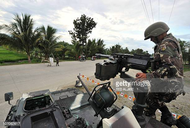A Philippine soldier inspects the gun of an armored personnel carrier at a check point near the massacre site in Ampatuan town Maguindanao province...