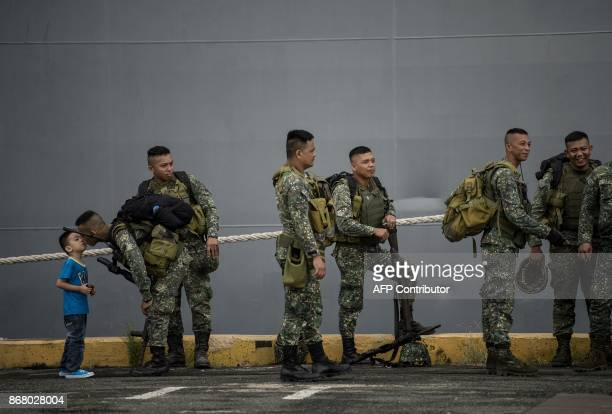A Philippine soldier kisses his son as he arrives at the port of Manila on October 30 with some 500 personnel composed of marines sailors aviators...