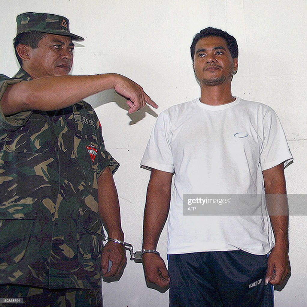 A Philippine soldier points to alleged Abu Sayyaf leader Usman Lijal when he was presented at a news conference in southern Zamboanga city 20 May 2004 following his arrest. Lijal linked by authorities to the abduction of three American tourists was captured together with a bodyguard during a raid in his hideout.
