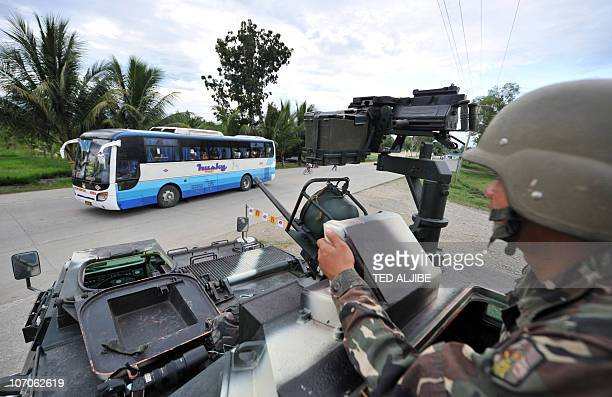 A Philippine soldier sits atop an armored personnel carrier while manning a check point near the massacre site in Ampatuan town Maguindanao province...