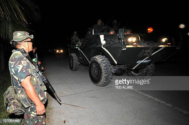 Philippine soldiers aboard an armored personnel carrier on a night patrol pass by a check point near the massacre site in Ampatuan town Maguindanao...