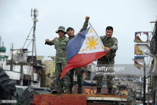 TOPSHOT Philippine soldiers aboard their armored personnel carrier celebrate after President Rodrigo Duterte declared Marawi City 'liberated' inside...