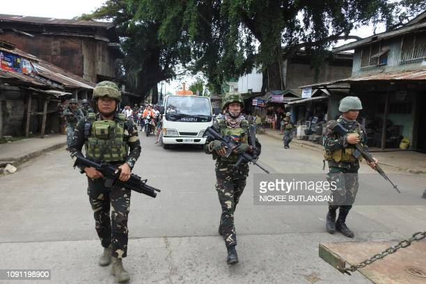 Philippine soldiers escort a hearse during the funeral procession of a victim killed in the January 27 cathedral bombing in Jolo Sulu province on the...