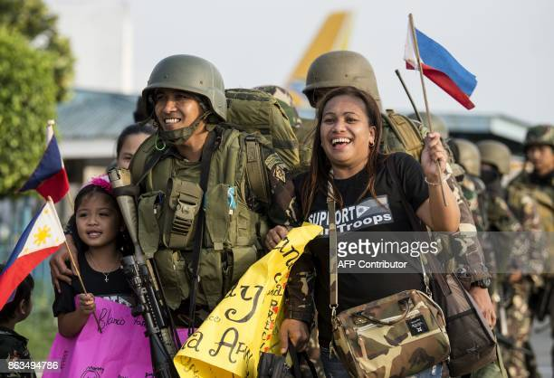 TOPSHOT Philippine soldiers from Marawi are welcomed home by their relatives at Villamor Airbase in Manila on October 20 2017 ProIS gunmen occupied...