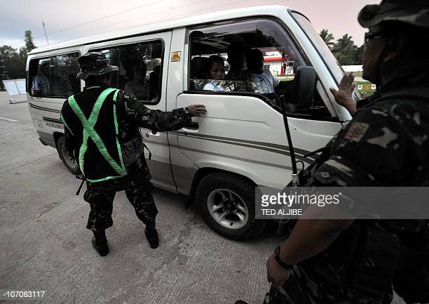 Philippine soldiers inspect passengers of a van at a check point near the massacre site in Ampatuan town Maguindanao province in southern island of...