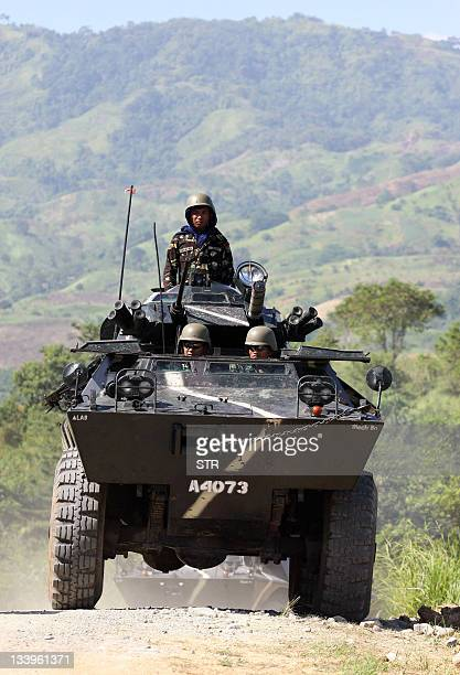 Philippine soldiers on board an armored personnel carrier patrol along the road leading to the site on November 23 2011 where 58 people 32 of them...