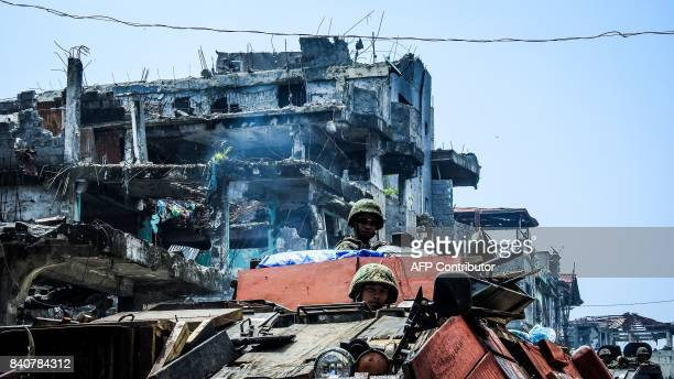 Philippine soldiers on board armoured personnel carriers move past damaged buildings in the Mapandi area of Marawi on the southern island of Mindanao...