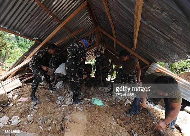 Philippine soldiers remove stones from a destroyed house as they help dig for survivors during a retreival operation on the slope of a mountain which...