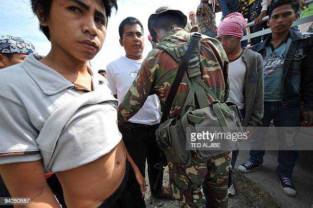 Philippine soldiers search passengers of a truck at a checkpoint in the town of Ampatuan in Maguindanao province on December 5 as the government...