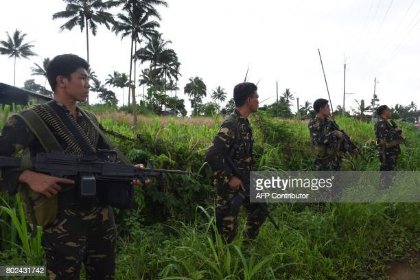 Philippine soldiers secure a road as they provide security for a retrieval operation of dead civilians in the outskirts of Marawi on the southern...