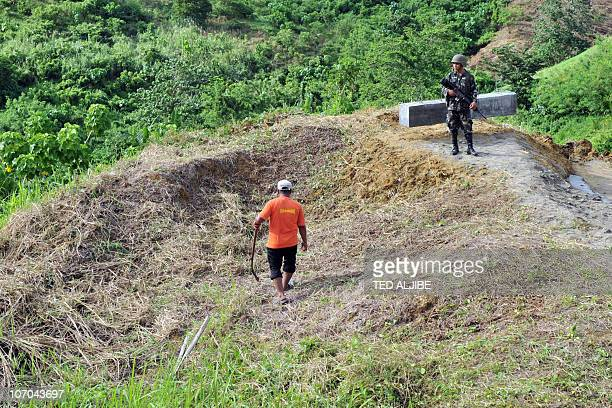 A Philippine soldiers stands guard next to a worker cutting grass at the November 23 2009 massacre site in the town of Ampatuan Maguindanao province...