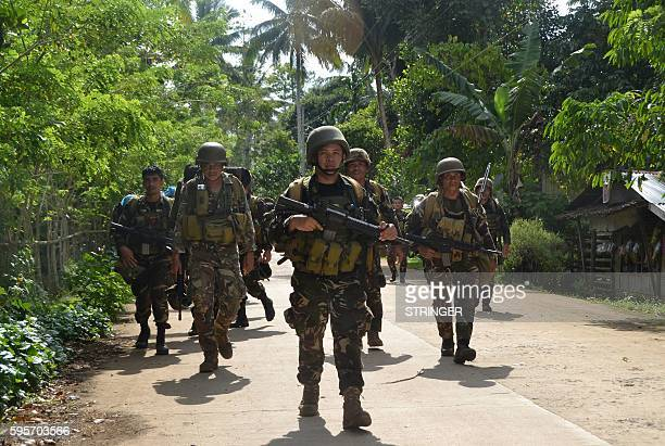 Philippine soldiers walk along a highway as they return to camp after an armed encouter with members of militant group Abu Sayyaf at the village of...