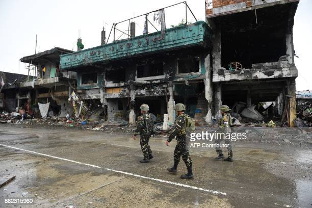 Philippine soldiers walk past bombedout buildings after attending a ceremony where President Rodrigo Duterte declared Marawi 'liberated' inside the...