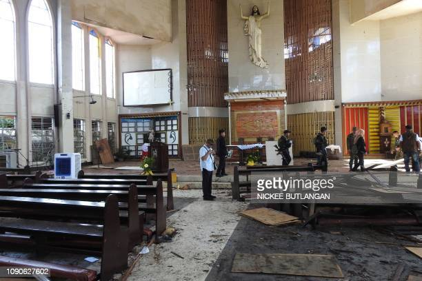 Philippine soldiers walk past the damage area of a catholic cathedral in Jolo town sulu province in southern island of Mindanao on January 28 a day...