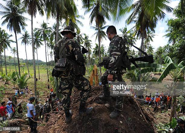 Philippine soldiers watch as recuers using a backhoe dig for survivors during a retrieval operation on the slope of a mountain which collapsed at the...