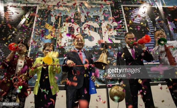TOPSHOT Philippine Stock Exchange officials blow horns and ring the bell to mark the New Year during the first day of trading at the PSE in Manila on...
