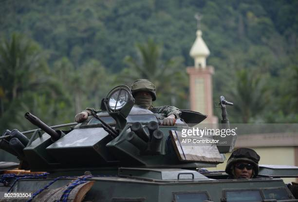 Philippine troops from the frontline drive past a mosque aboard their armoured personnel carrier in the outskirts of Marawi on the southern island of...