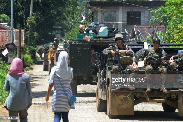 Philippine troops looks on at local residents as they on their military vehicles towards the frontline in the outskirts of Marawi on the southern...