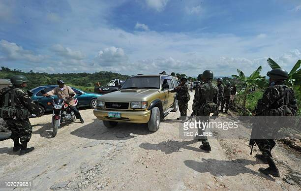 Philippine troops man at a checkpoint along the road leading to the massacre site in the town of Ampatuan in Maguindanao province in southern island...