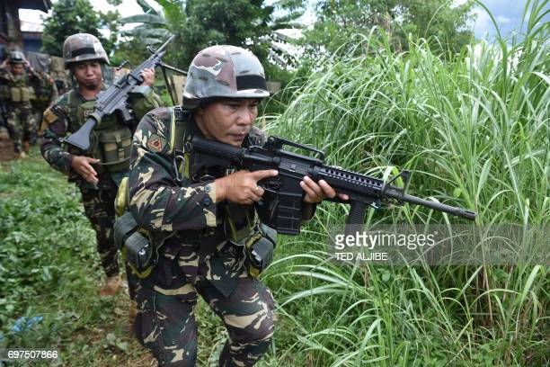 TOPSHOT Philippine troops patrol a grassy area near the frontline in Marawi on the southern island of Mindanao on June 19 as the armed conflict...