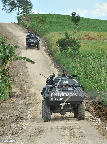 Philippine troops patrol along the road leading to the November 23 2009 massacre site in the town of Ampatuan Maguindanao province on November 21...