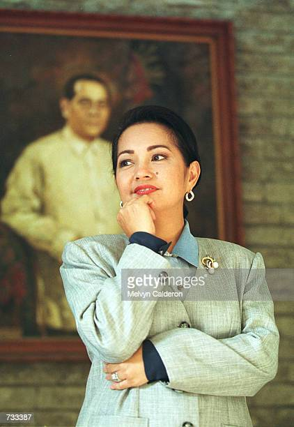 Philippine Vice President Gloria Macapagal Arroyo poses for a photograph in front of a painting of her father, former President Diosdado Macapagal,...