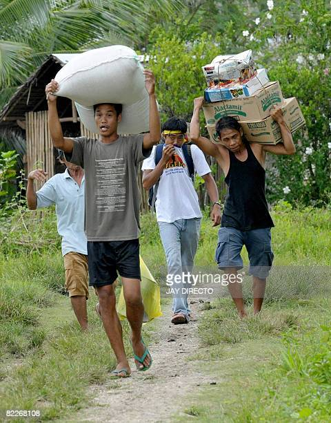 Philippine villagers carry their belongings as they evacuate from the remote village of Takepan in North Cotabato Province southern Philippines on...