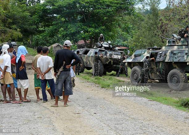 Philippine villagers watch as army reinforcements arrive in the remote village of Bagolibas in North Cotabato province, southern Philippines on...