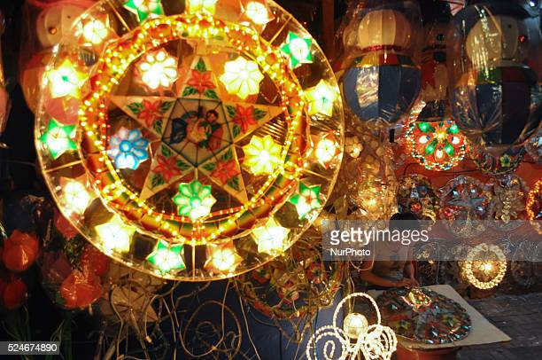 manila philippines a lantern shines brightly as a stall attendant works on a capiz lantern at