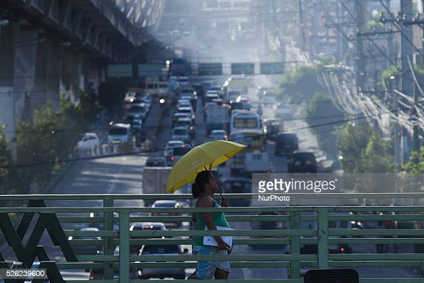MANILA Philippines A woman crosses on an elevated footbridge to avoid the rampage of vehicles along a busy highway in Quezon City north of Manila on...