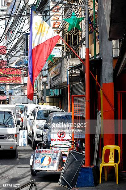 philippines flag on building by cars at street - philippines flag stock pictures, royalty-free photos & images