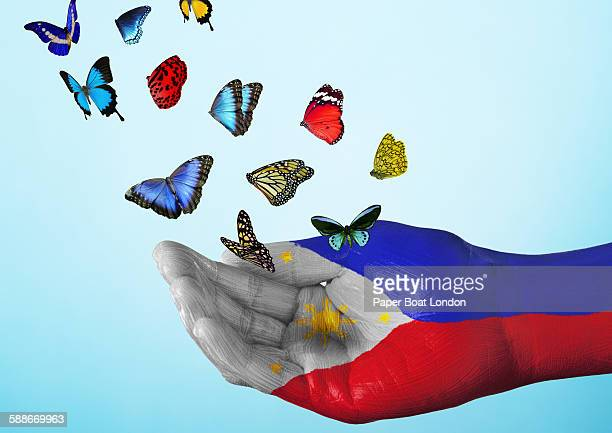 philippines flag painted on hand with butterflies - filipino culture stock pictures, royalty-free photos & images