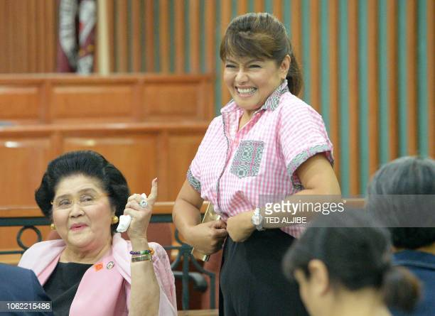 Philippines' former first lady Imelda Marcos gestures beside her daughter Imee as she waits for the release order from the graft court following her...