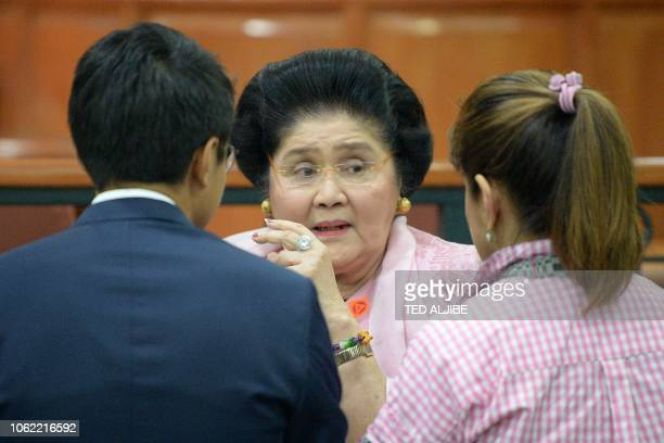 Philippines' former first lady Imelda Marcos talks to her daughter Imee after attending a hearing at the graft court in Manila on November 16 2018