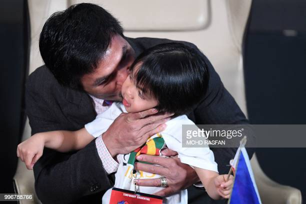 Philippine's Manny Pacquiao kisses his son Israel during a press conference in Kuala Lumpur on July 12 ahead of his world welterweight boxing...