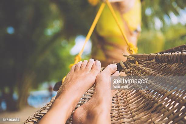 Philippines, Palawan island, Port Barton, Feet of a woman in a cane hammock