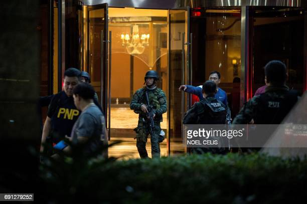 Philippines' police officers come out from the Resorts World Hotel in Manila on June 2 2017 following an assault A gunman was on the loose at a...