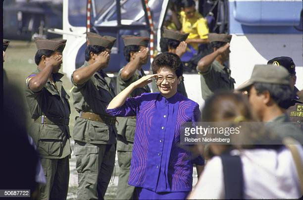 Philippine's Pres. Corazon Aquino saluting troops during rally favoring ratification of constitution.